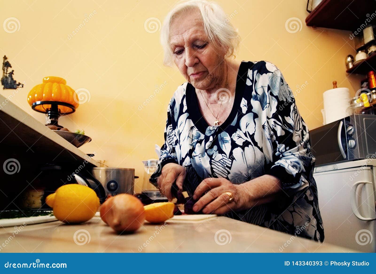En gammal kvinna lagar mat