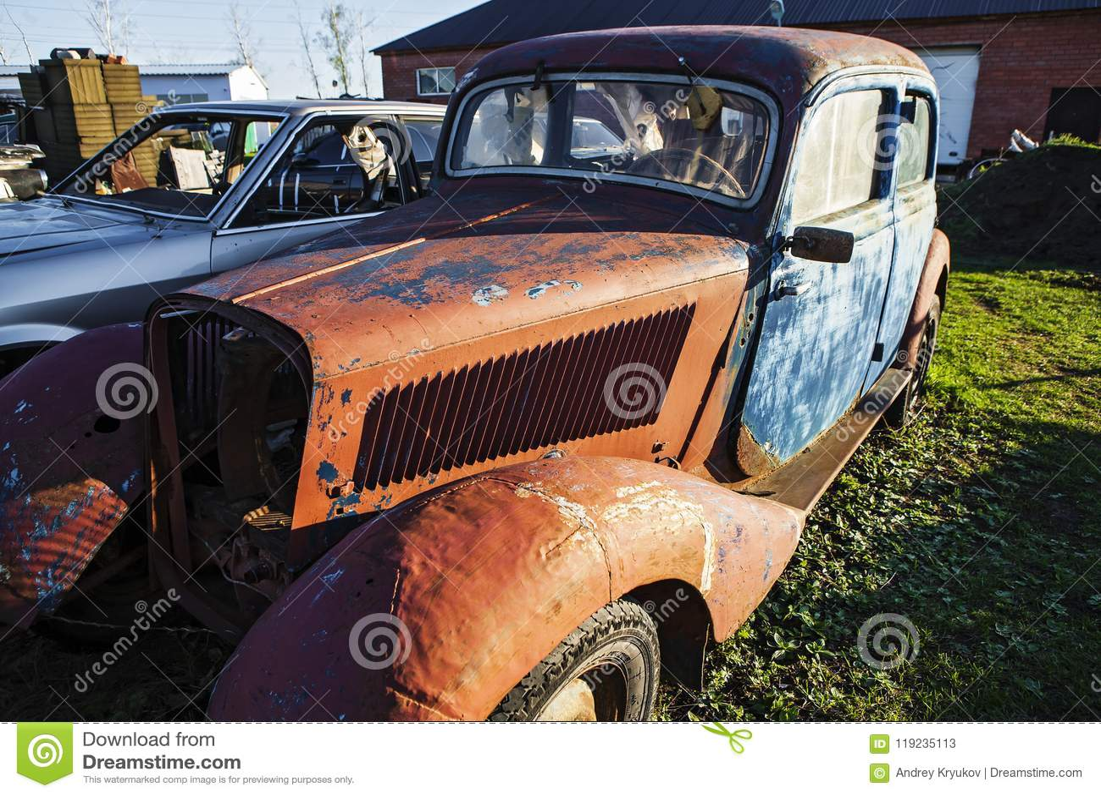 En gammal rostig bil i en bilförrådsplats