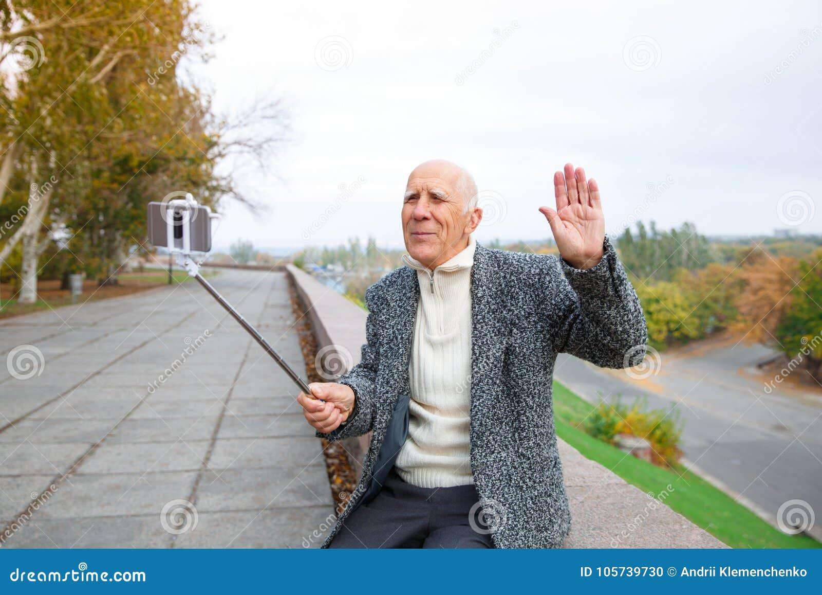 En gladlynt gamal man sitter på par, en vinkande hand och ett innehav en mobiltelefon med en monopod