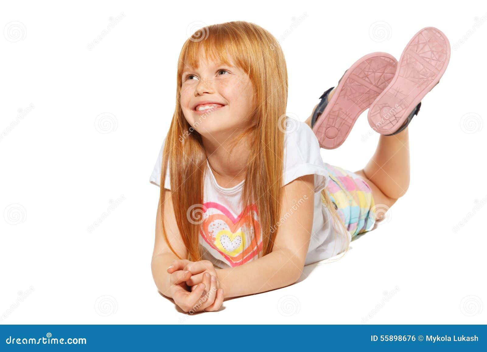 En gladlynt liten flicka med rött hår ligger; isolerat på den vita bakgrunden