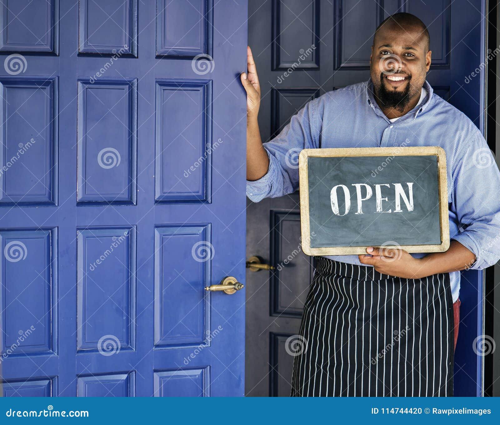 En gladlynt små och medelstora företagägare med det öppna tecknet