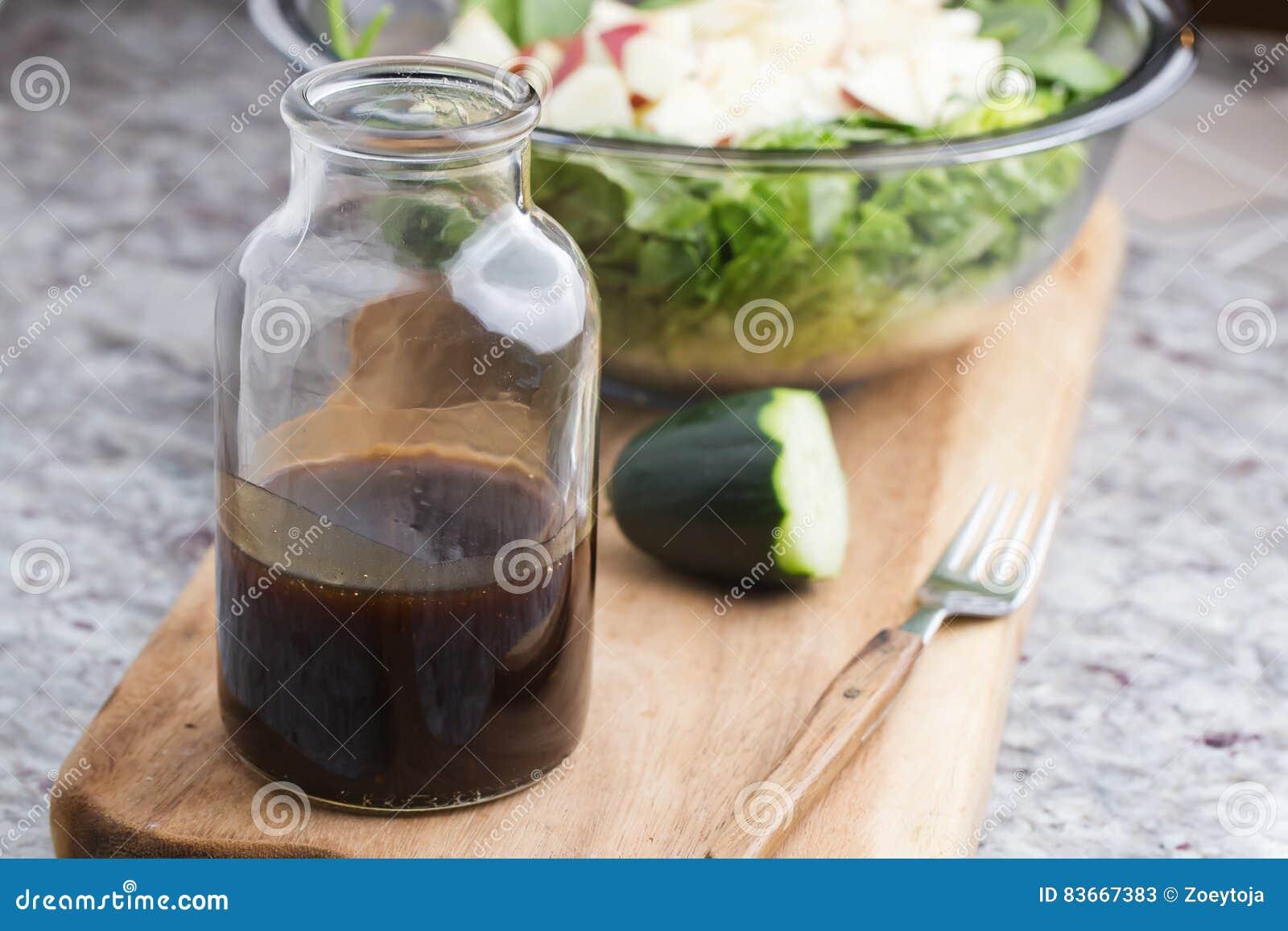 En glasflaska med dressingen som består av balsamic vinäger, honung och olivolja