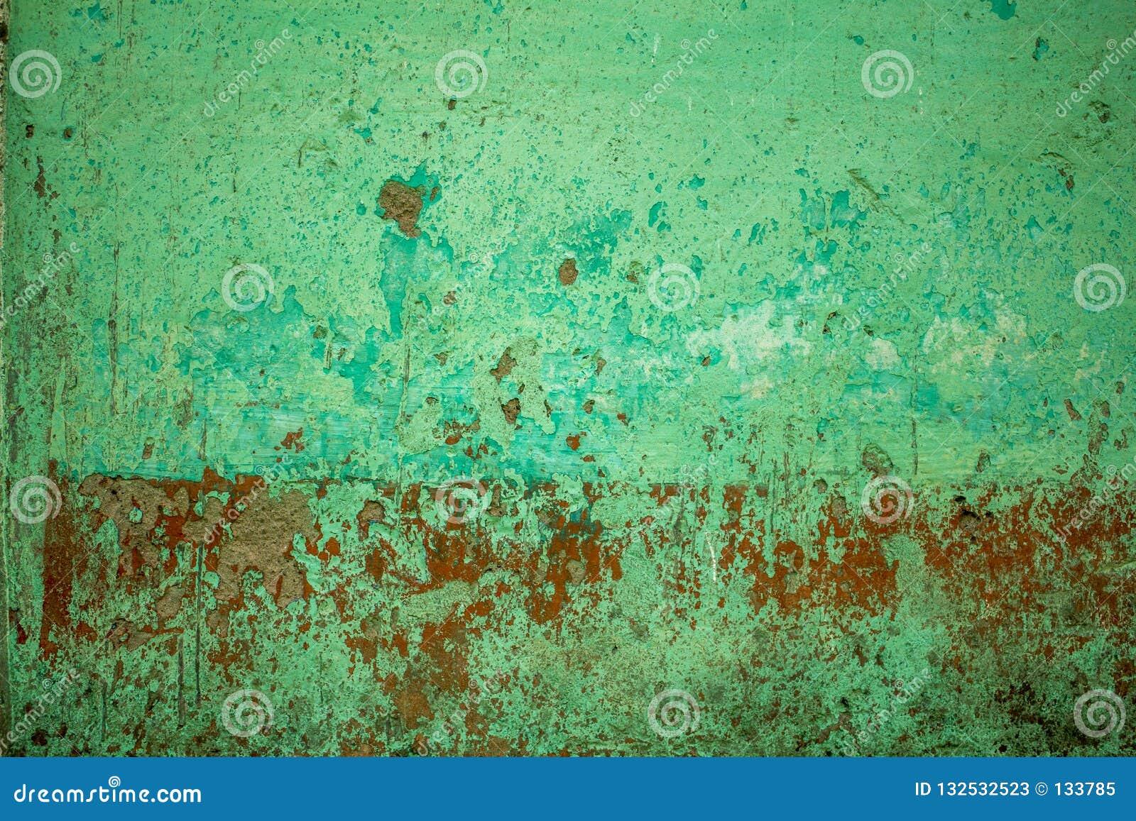 En grön röd gammal betongvägg med djupa skrapor och skada Textur för grov yttersida målarfärg- och smutsfläckar