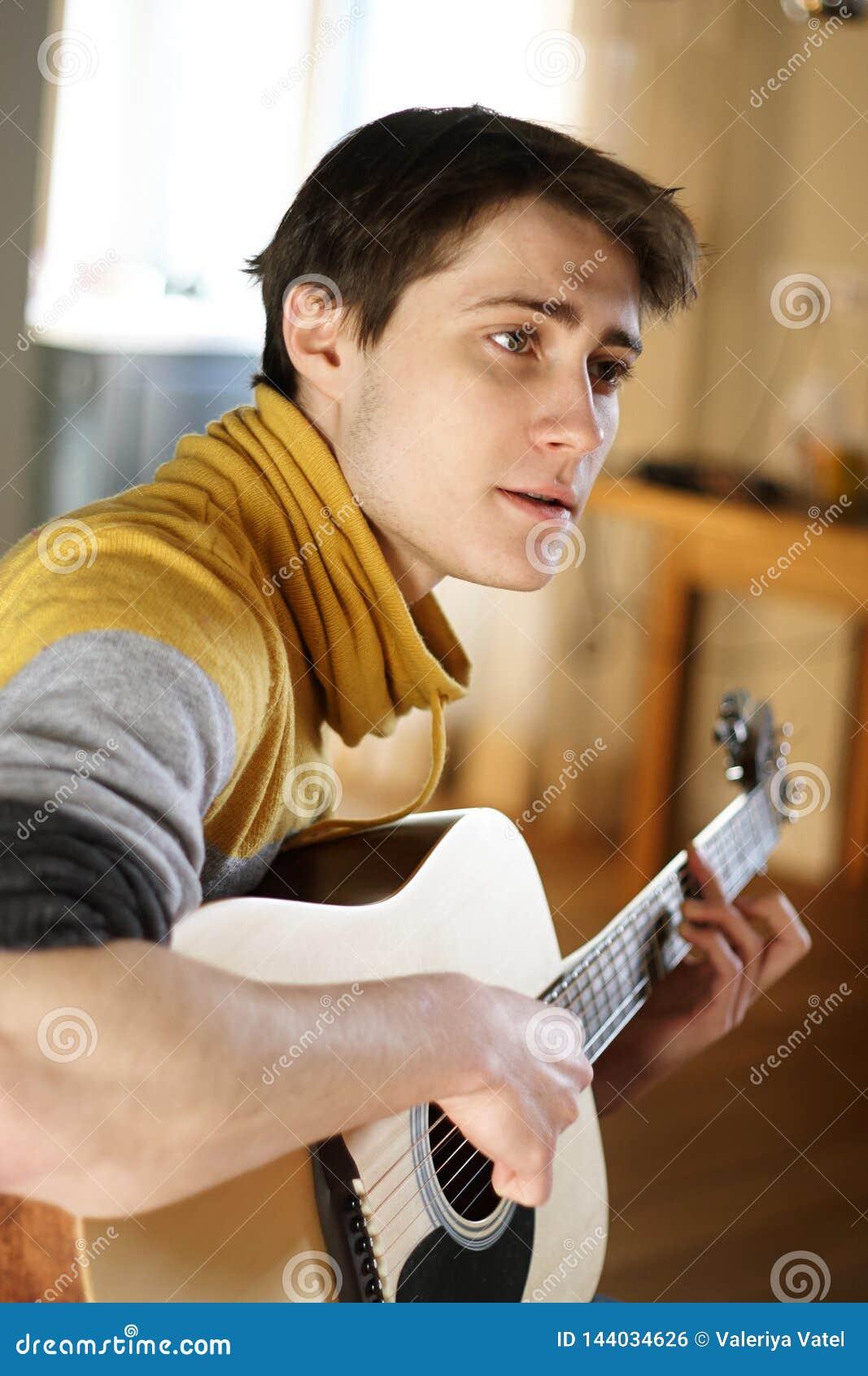 En grabb i en gul tröja sjunger en sång som spelar på hans gitarr