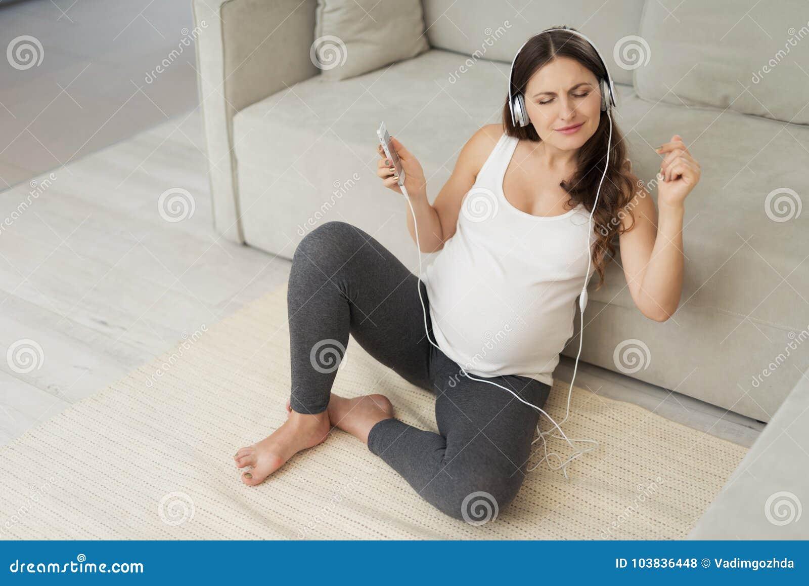 En gravid kvinna sitter på ett ljust golv hemma Hon bar hörlurar och lyssnade till musik