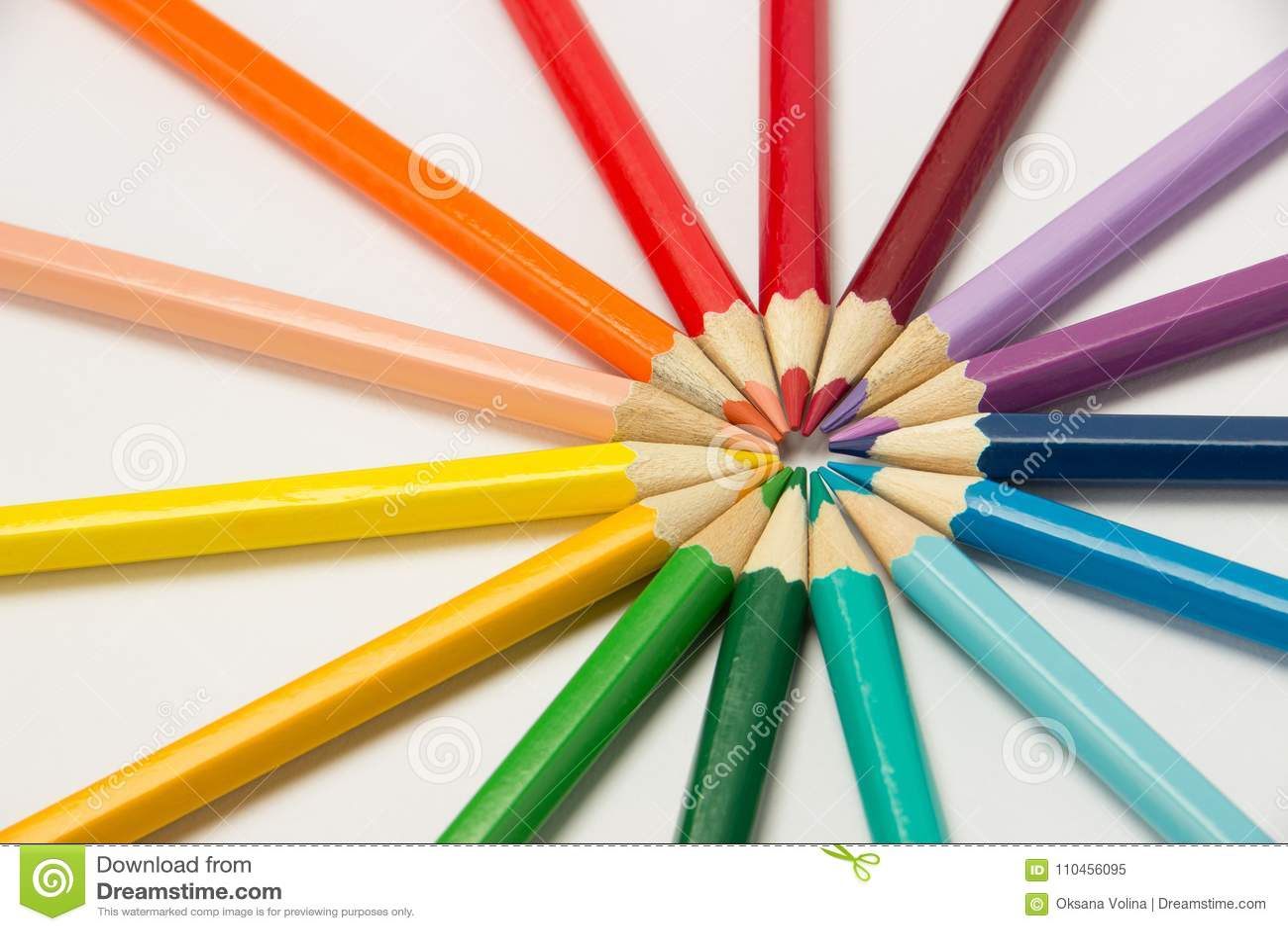 En grupp av blyertspennor vek i regnbågefärger i en cirkel på en whi