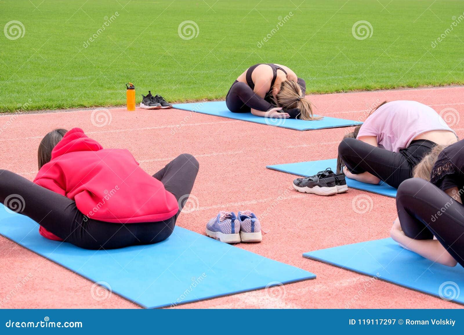 En grupp av flickor utför konditionövningar i den öppna luften tillbaka sikt Övning för sträckning i lotusblommapositionen