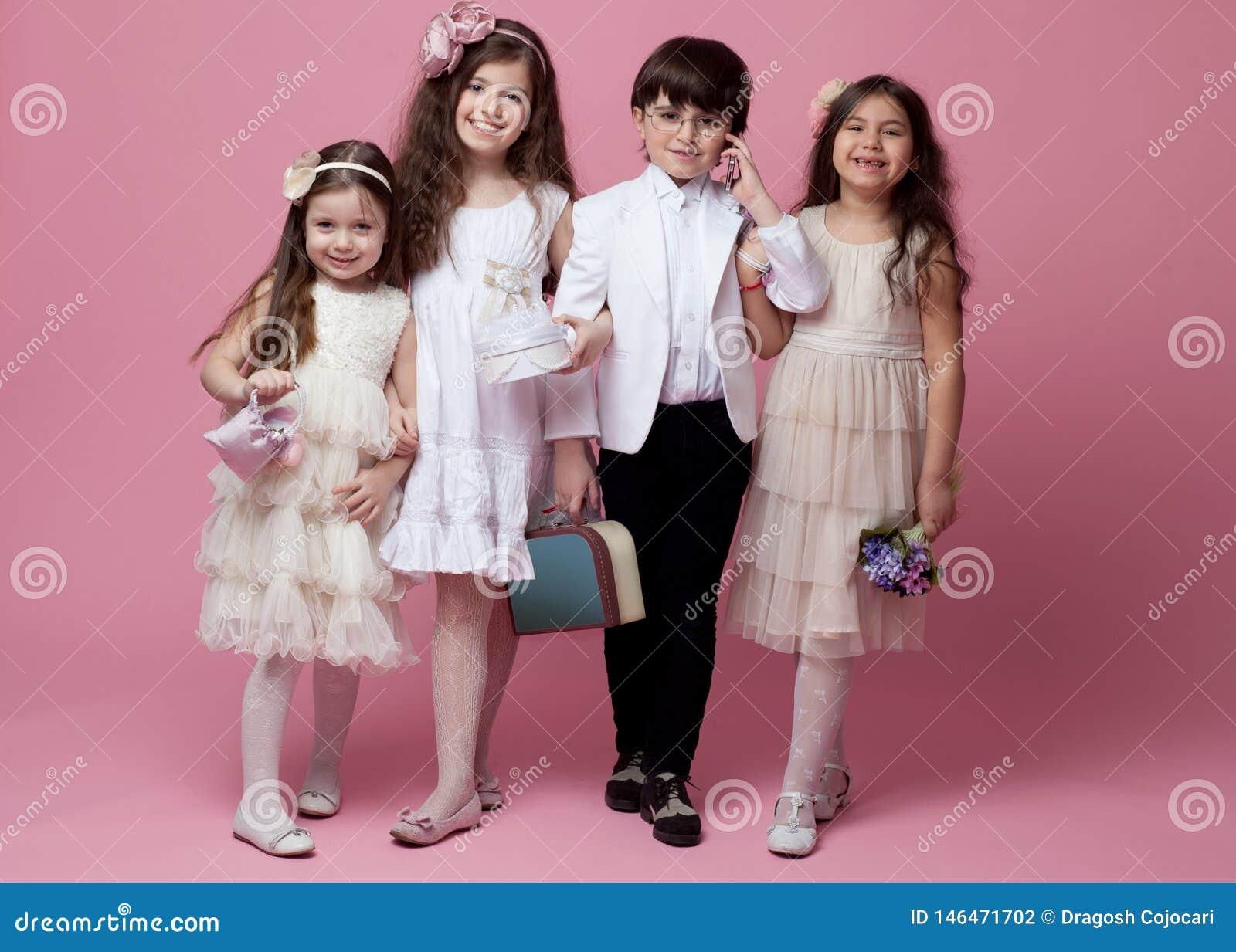 En grupp av iklädda härliga klassiska tappningkläder för lyckliga barn som isoleras på rosa bakgrund