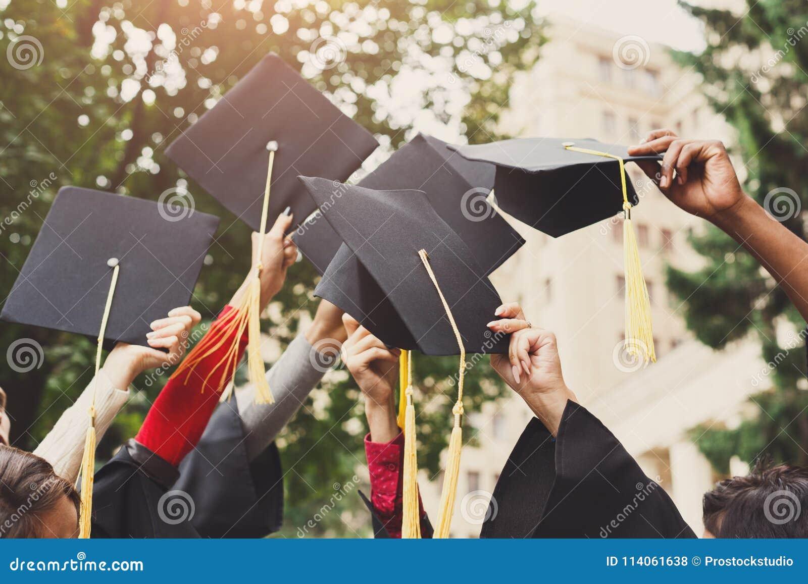 En grupp av kandidater som kastar avläggande av examenlock i luften