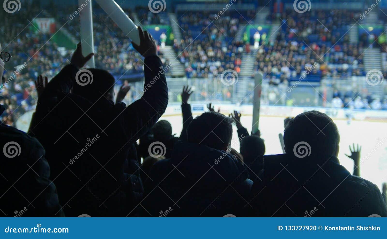 En grupp av matchen för ungdomarden hållande ögonen på hockey ovation