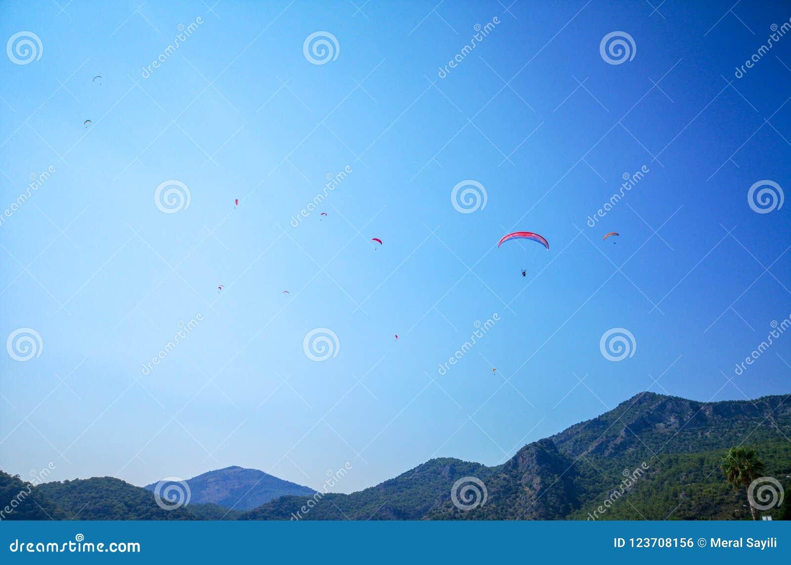 En grupp av parachuters som högt flyger ovanför en grön kulle i den blåa himlen för sommartid, Fethiye, Mugla