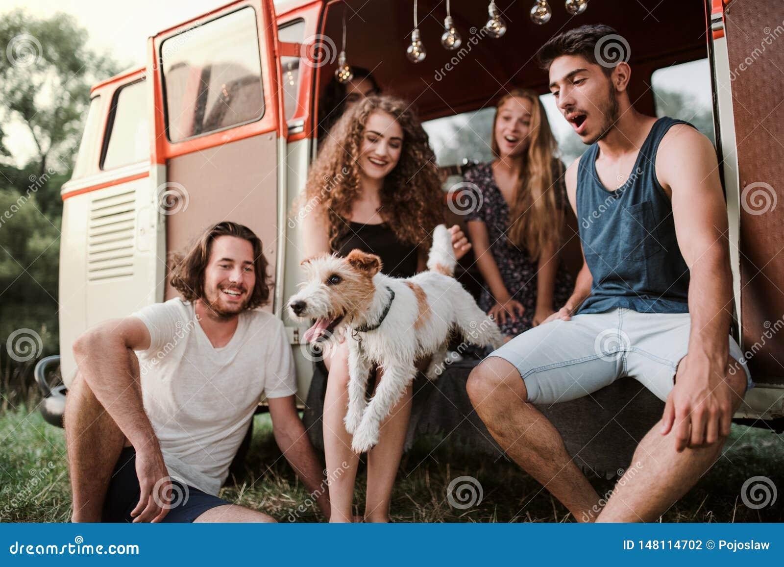 En grupp av unga vänner med en hund på en roadtrip till och med bygd
