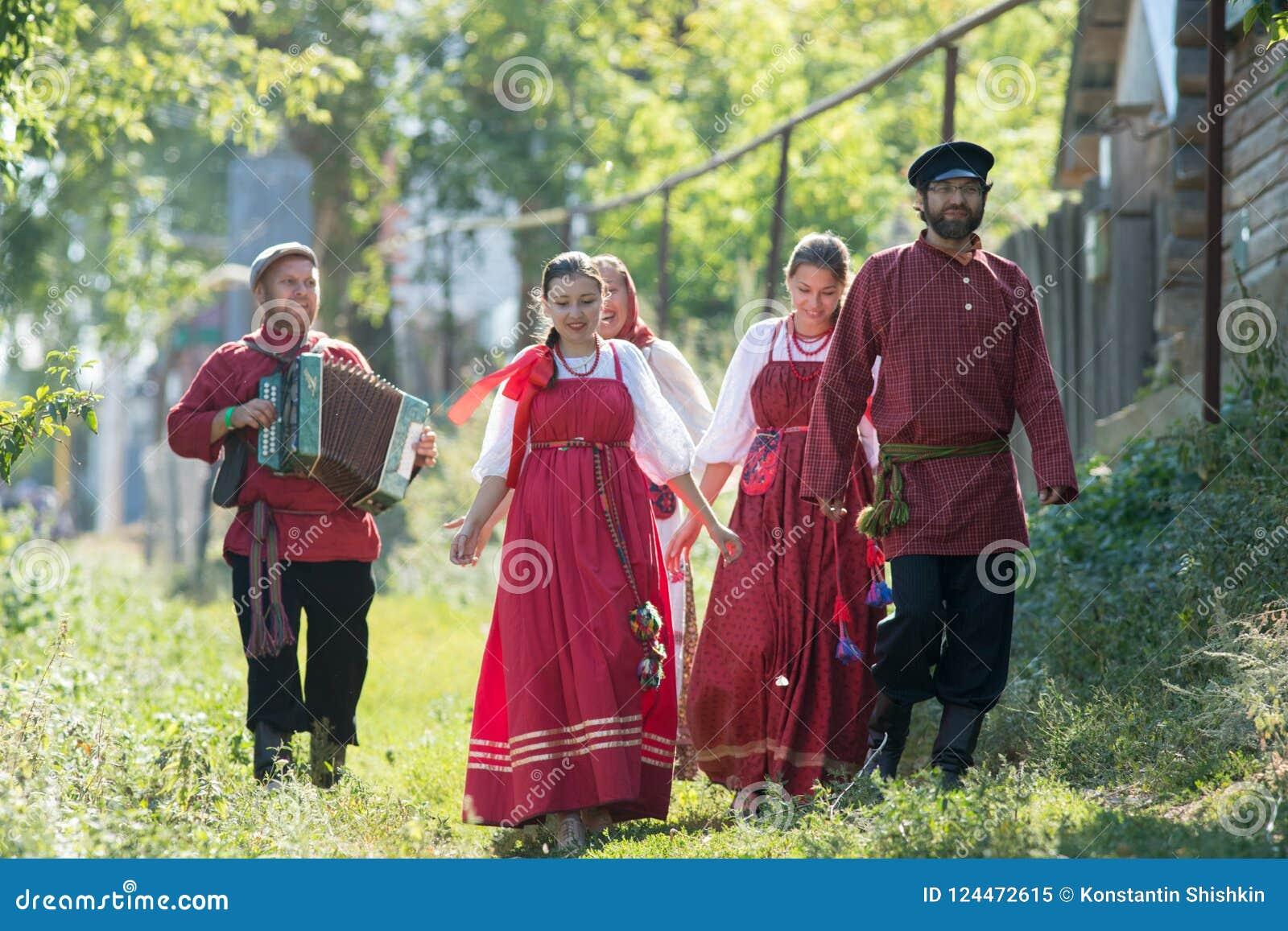 En grupp av ungdomari rysk medborgare kostymerar att gå runt om byn