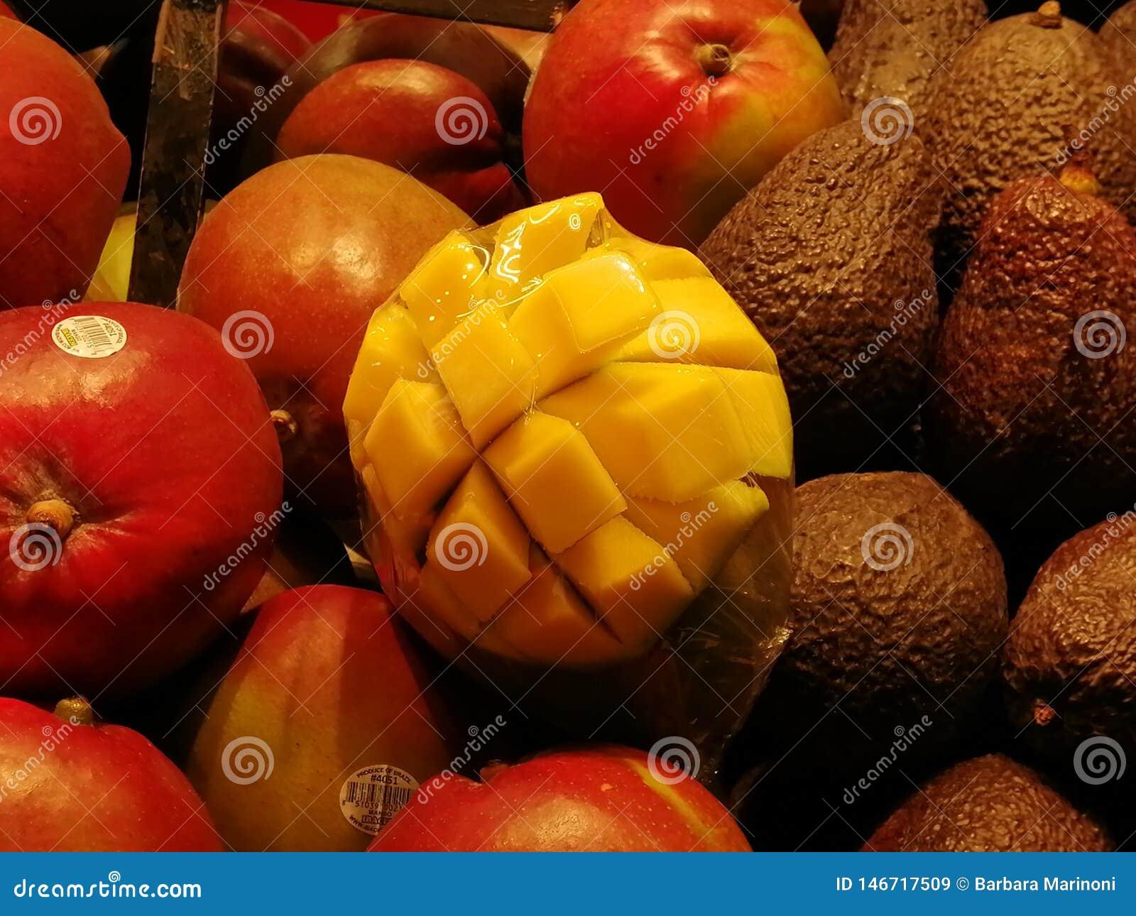 En gul mango i en fruktkorg