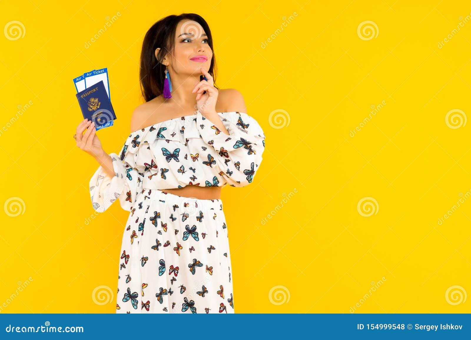 En gullig asiatisk kvinna i en siden- klänning med fjärilar rymmer ett pass och flygbiljetter på en gul bakgrund