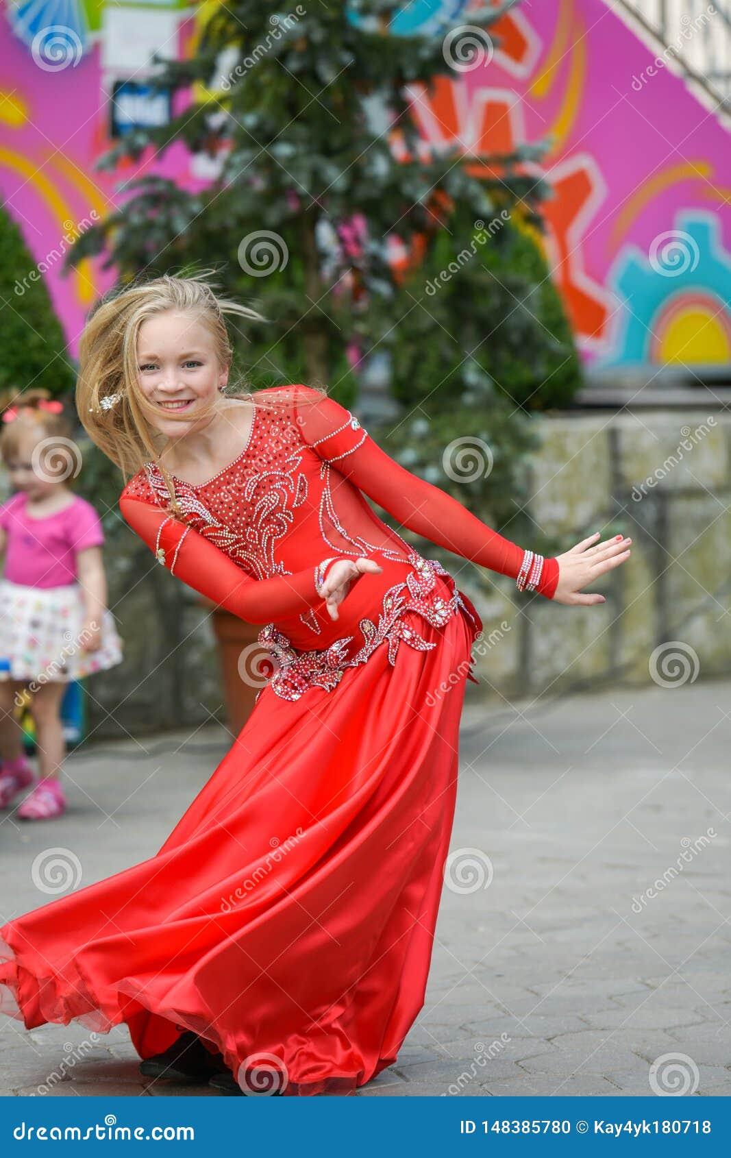 En gullig liten flicka i en röd dräkt dansar på gatan Flicka i dansgruppen Behandla som ett barn flickan lär dans Showdans till