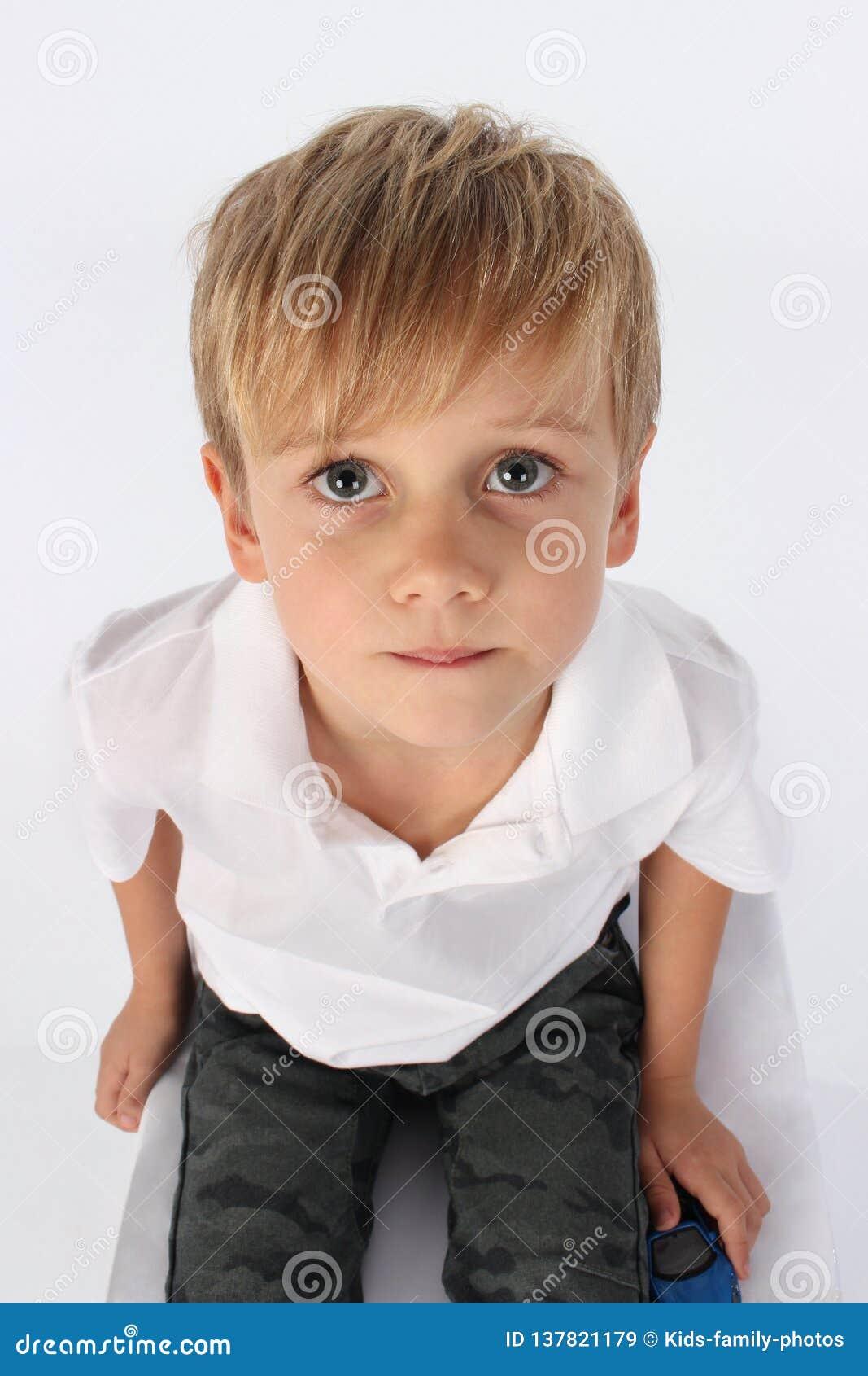 En gullig stilig preteen pojke som innocently sitter och uppriktigt och ser