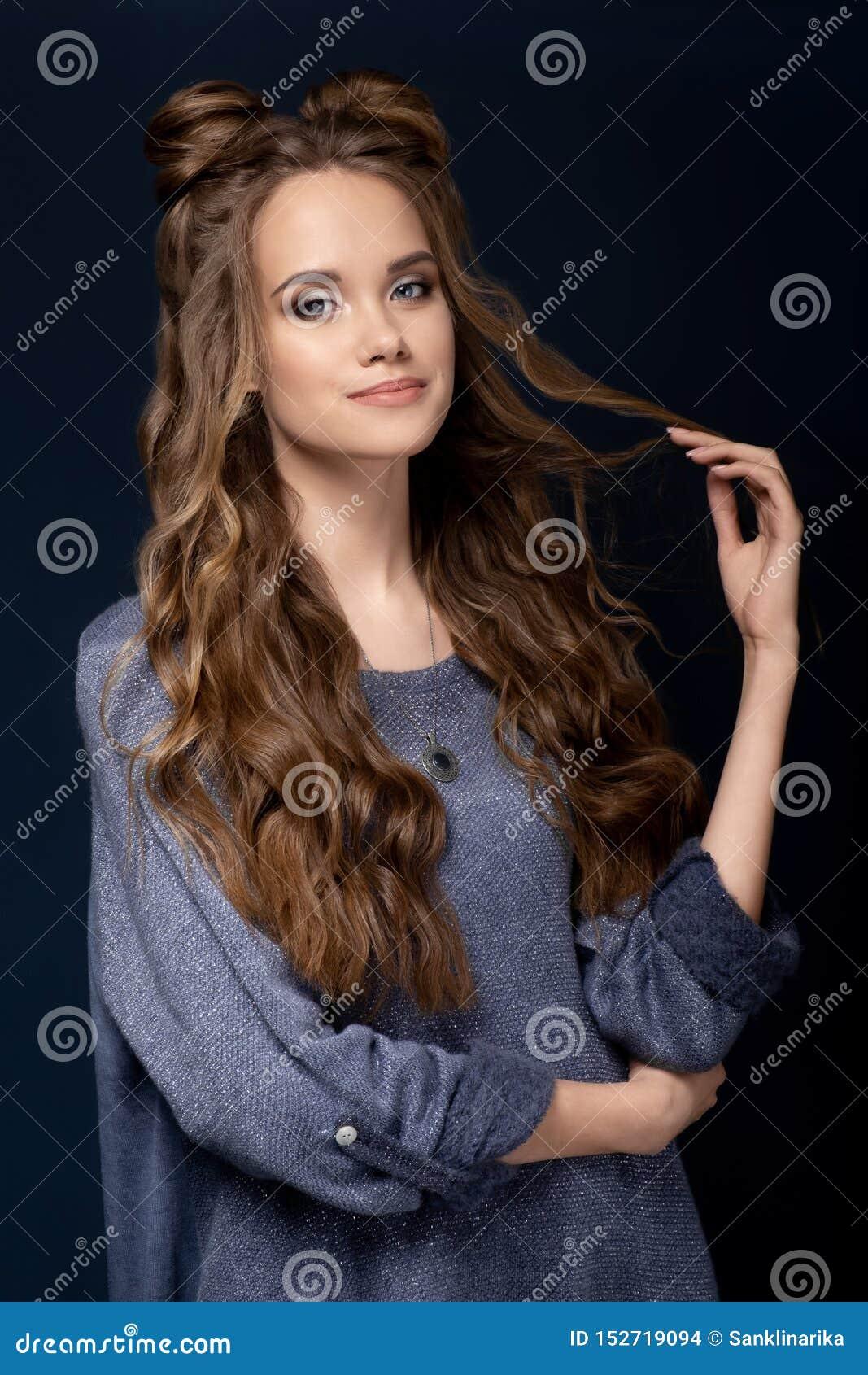 En gullig ung flicka i en blå stucken klänning på en blå bakgrund med en frisyr och ett lockigt långt hår