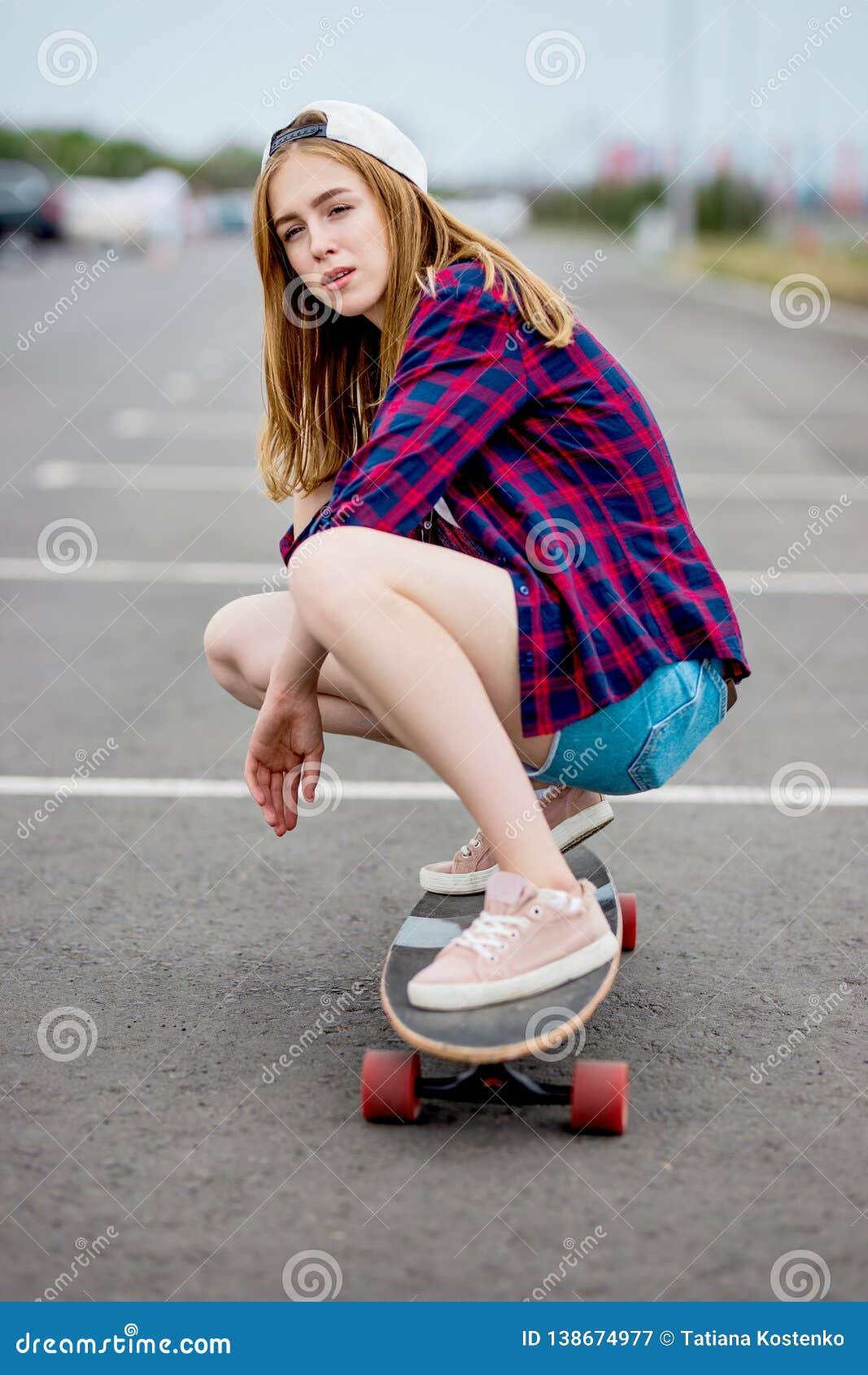 En härlig blond flicka som bär rutiga skjorta-, lock- och grov bomullstvillkortslutningar, sitter på longboarden på parkeringshus