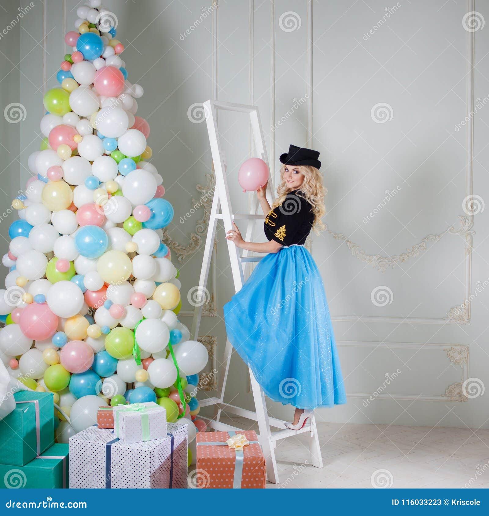 En härlig blondin i en karnevaldräkt dekorerar trädet av ballonger Den charmiga unga kvinnan i en curvy blått kringgår