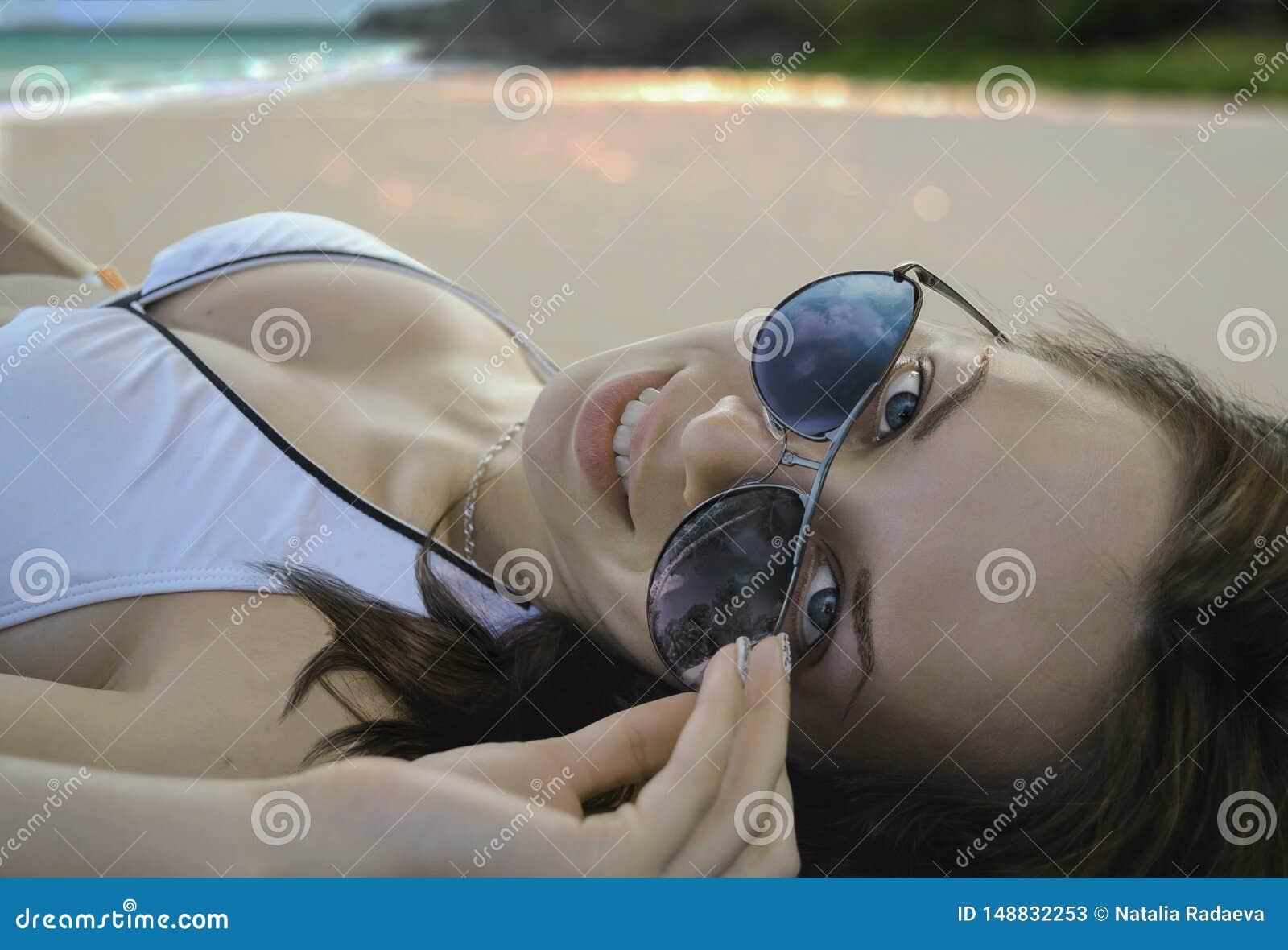 En h?rlig Caucasian kvinnlig i den vita bikinin som ligger p? en sandig strand vid havet, ler och rymmer hennes solglas?gon A