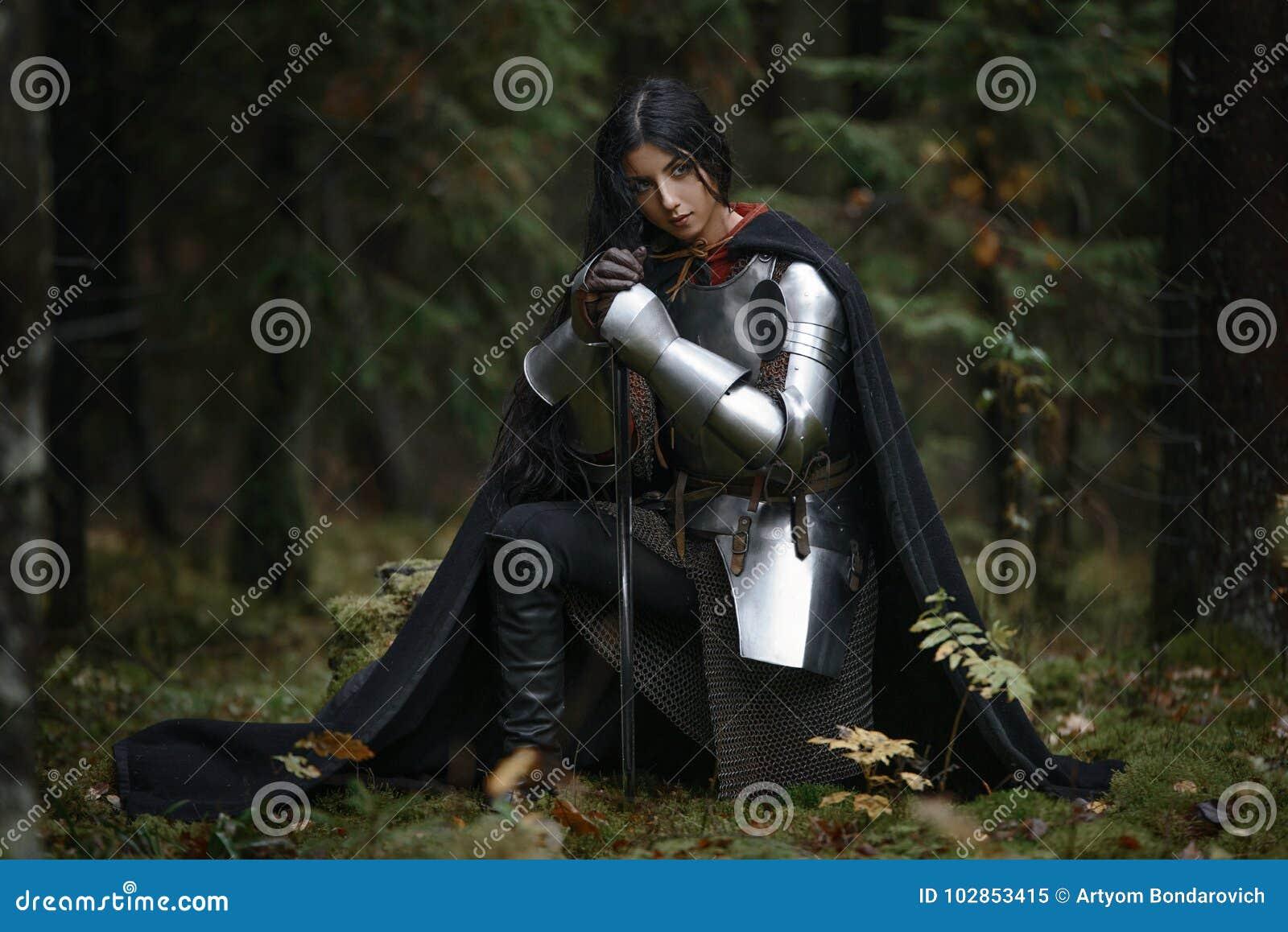 En härlig krigareflicka med en bärande chainmail för svärd och harnesk i en mystisk skog