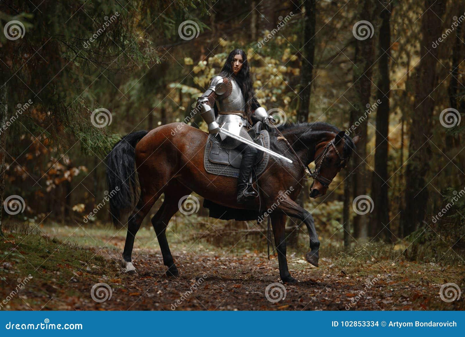 En härlig krigareflicka med en bärande chainmail och harnesk för svärd som rider en häst i en mystisk skog