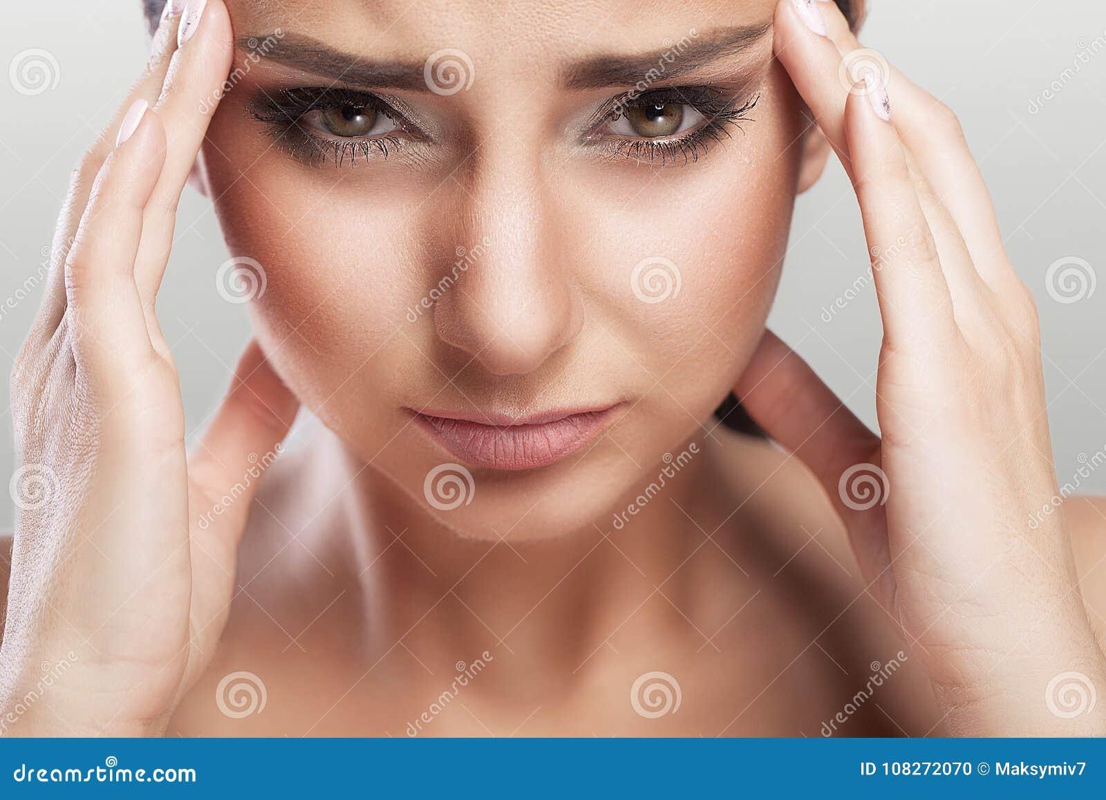 En härlig kvinna på en grå bakgrund, spänning och huvudvärk med migränhuvudvärker, brottades hon med smärtar, en stor stående, hö
