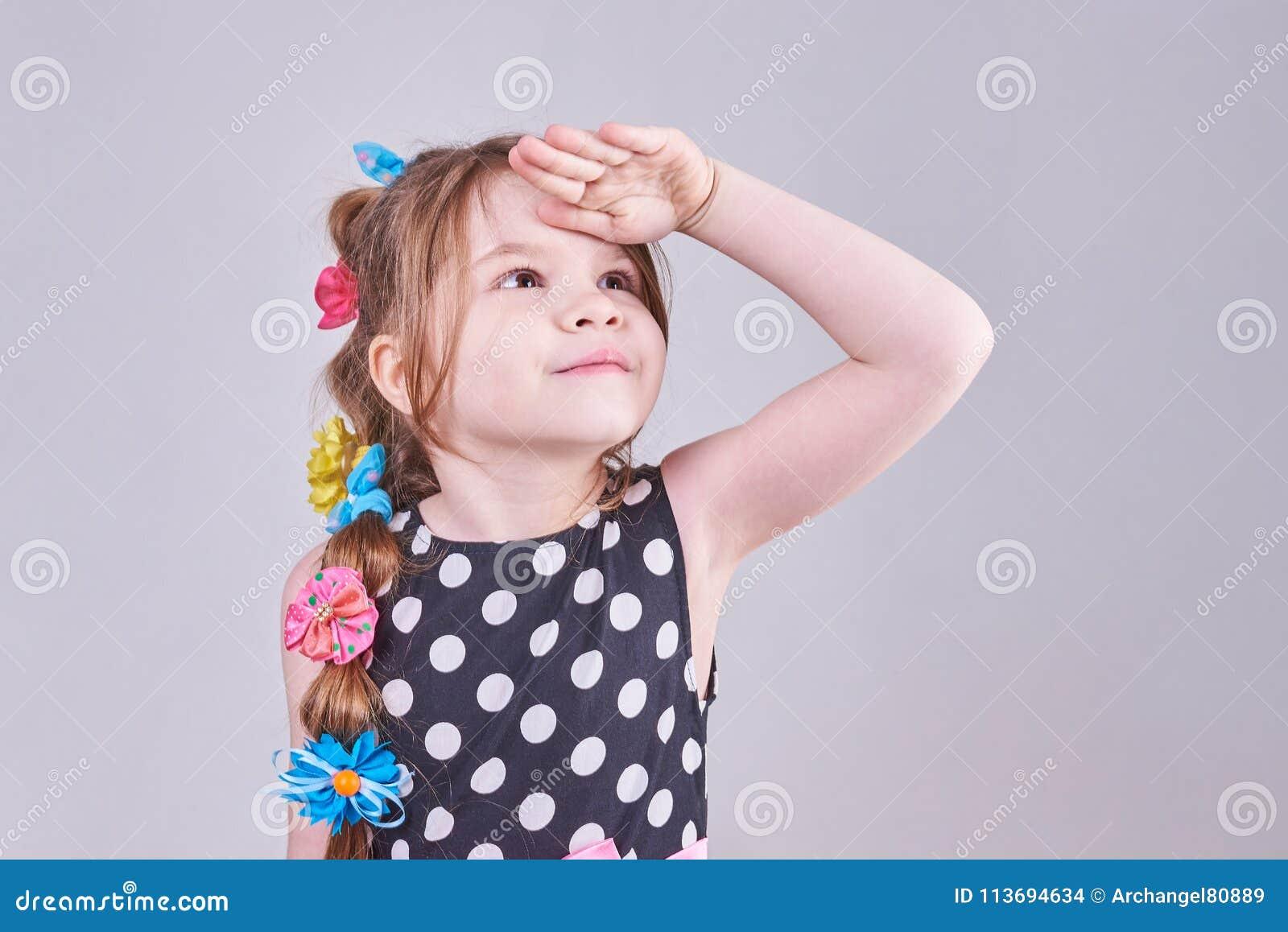 En härlig liten flicka ser upp och att sätta hennes hand till hennes panna