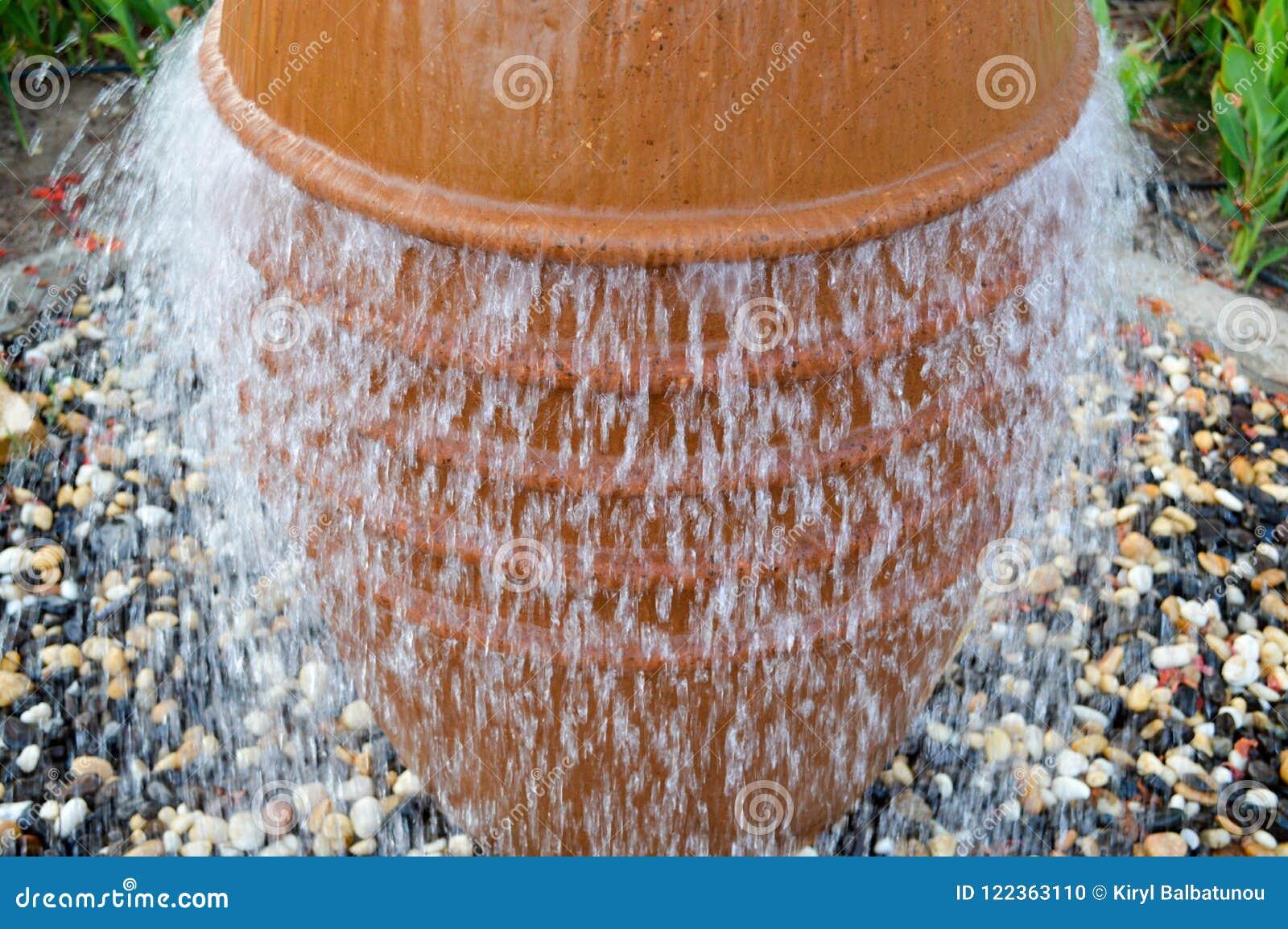 En härlig liten springbrunn i form av en brun vas, en tillbringare med fallande droppar av vatten på kulört stå för stenar
