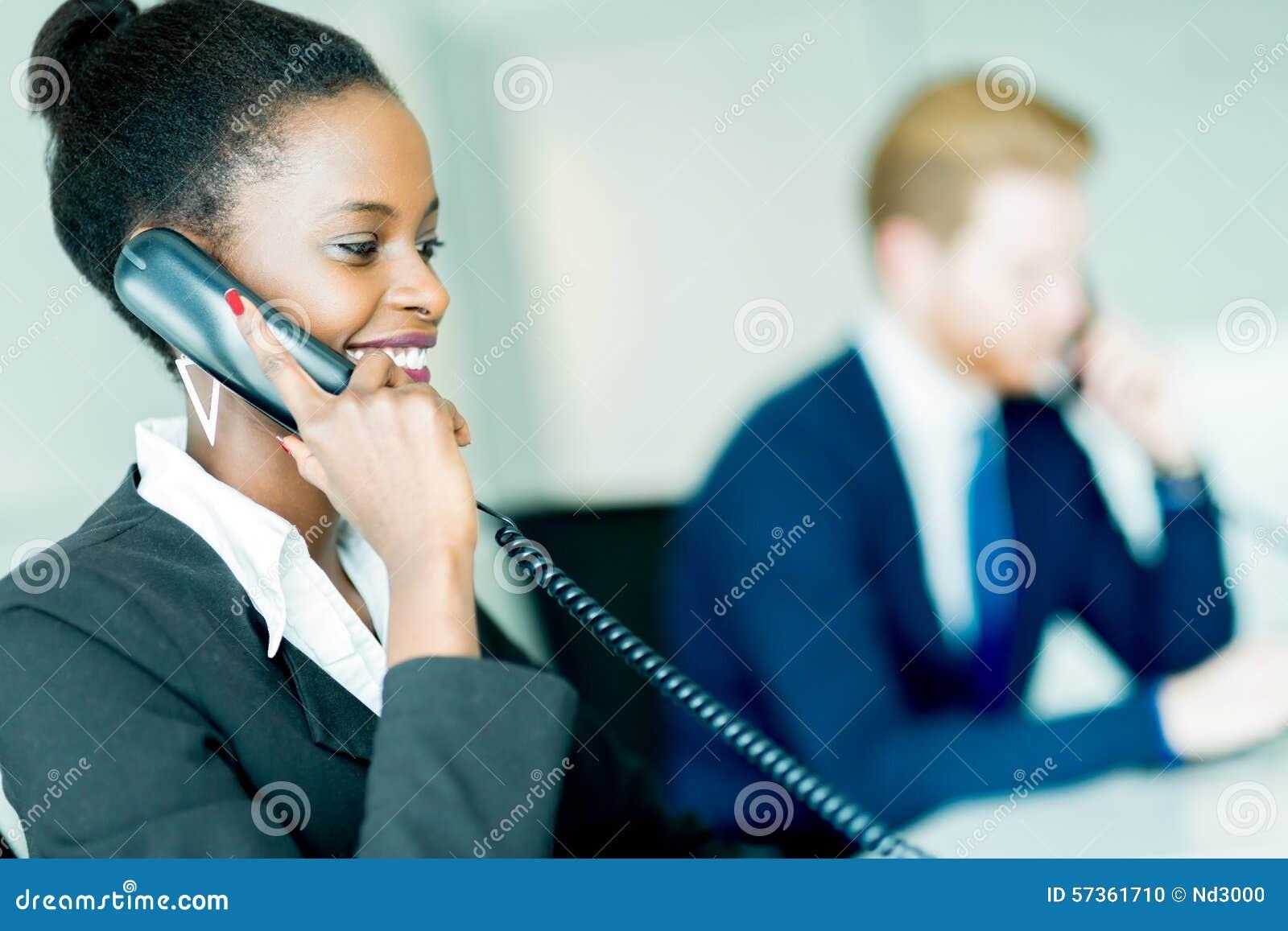 En härlig, svart ung kvinna som arbetar på en appellmitt i en nolla