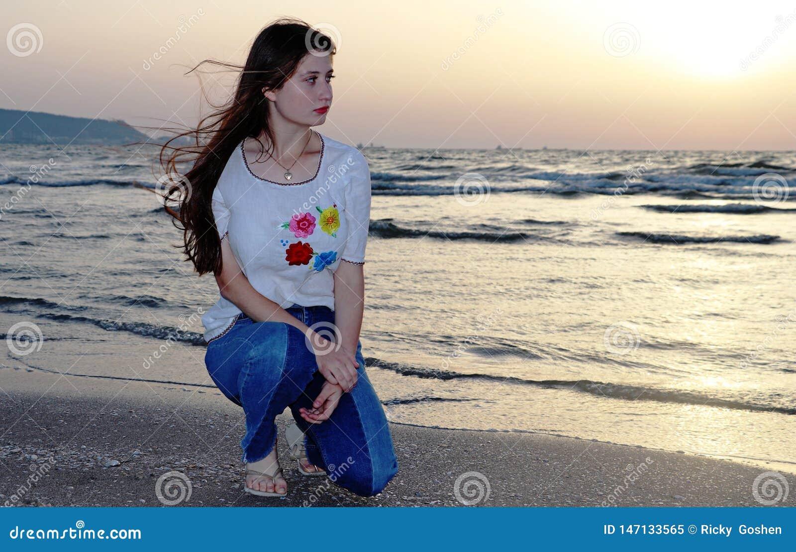 En härlig tonårs- flicka sitter på stranden