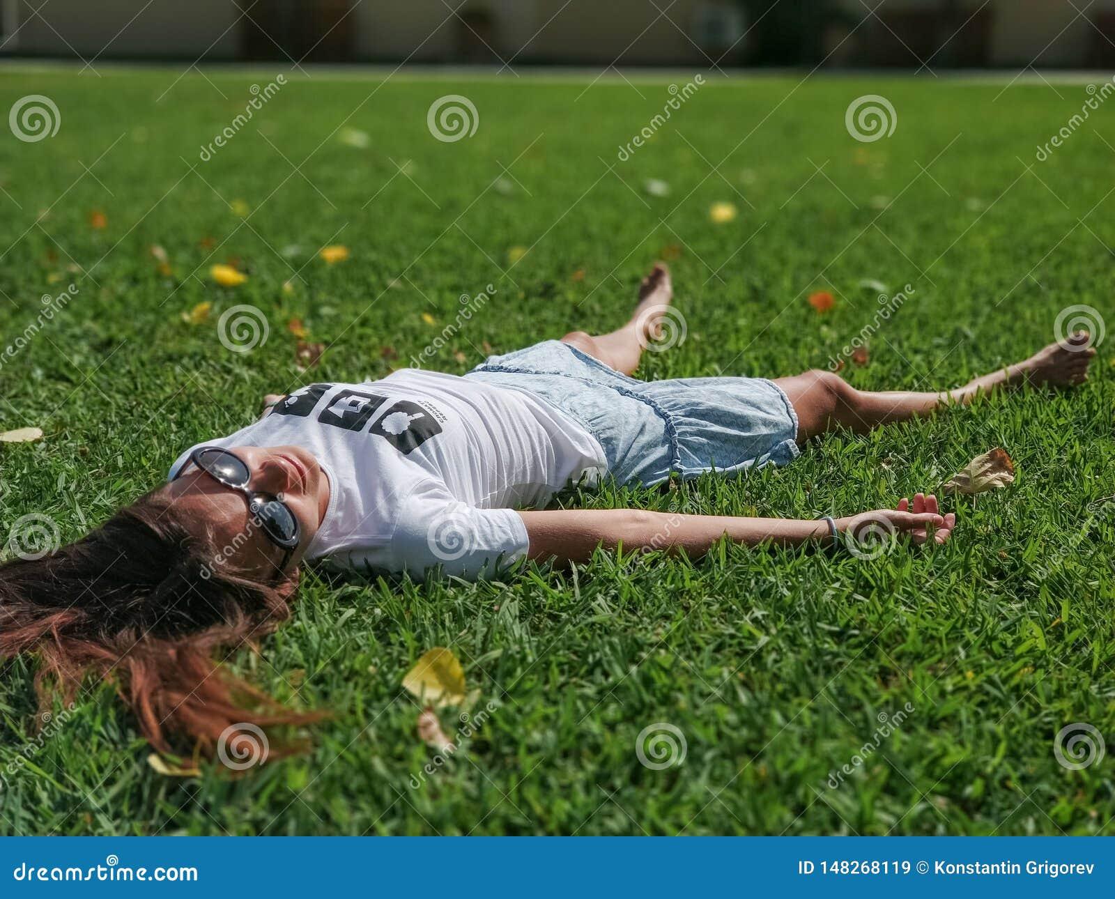 En härlig ung flicka i en vit T-skjorta med inskriftavbrottet ett träd och en kjol ligger på gräset