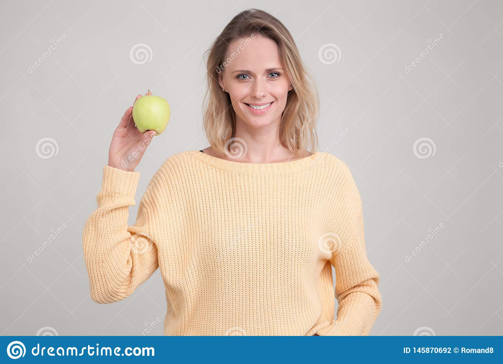 En härlig ung flicka med blont hår ler på kameran och rymmer ett grönt äpple i hennes hand hon är iklädd en guling
