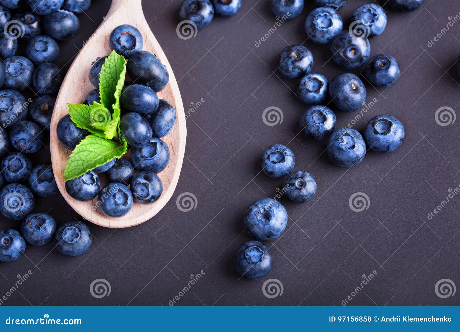 En hög av blåbär med den gröna mintkaramellen i en träsked på en purpurfärgad bakgrund Healthful ingredienser för sommarfruktsall