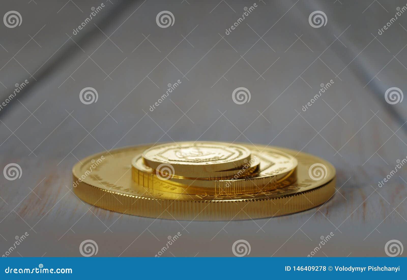 En hög av guld- mynt av olika format på en suddig bakgrund