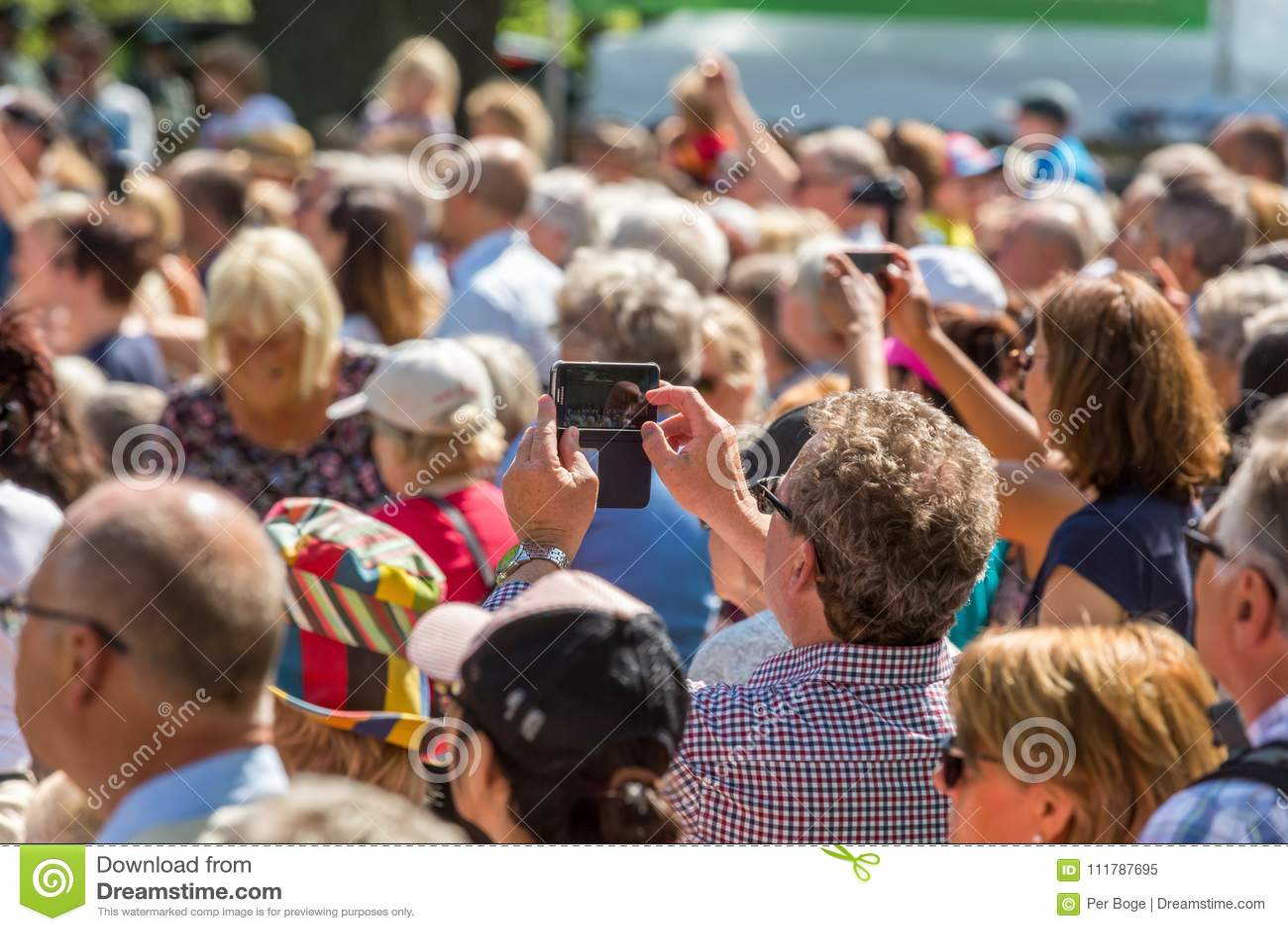 En hög kvinna som rymmer en mobiltelefon som tar bilder