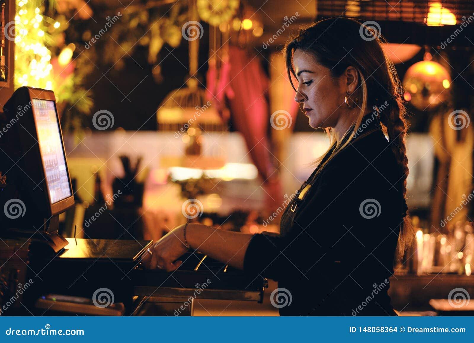 En h?rlig ung kvinna p? skrivbordet i en restaurang