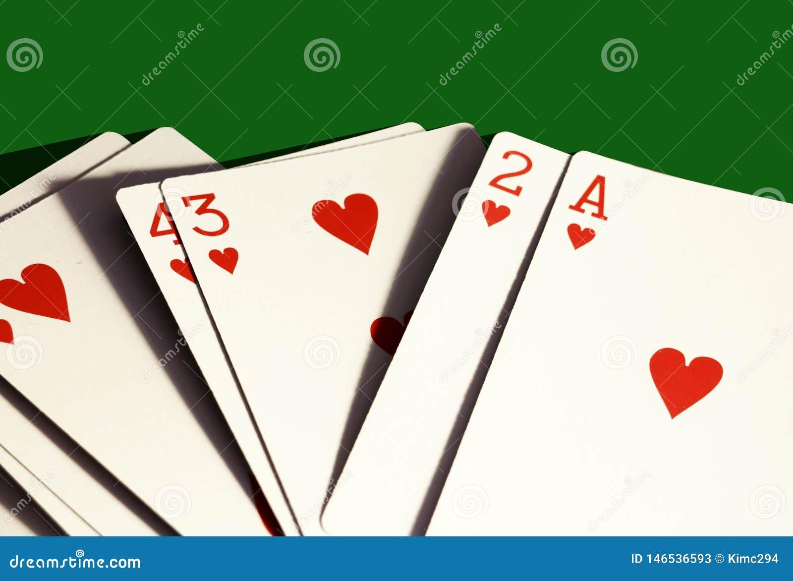 En hand av hjärtor som spelar endast kort på mörkt - grön bakgrund