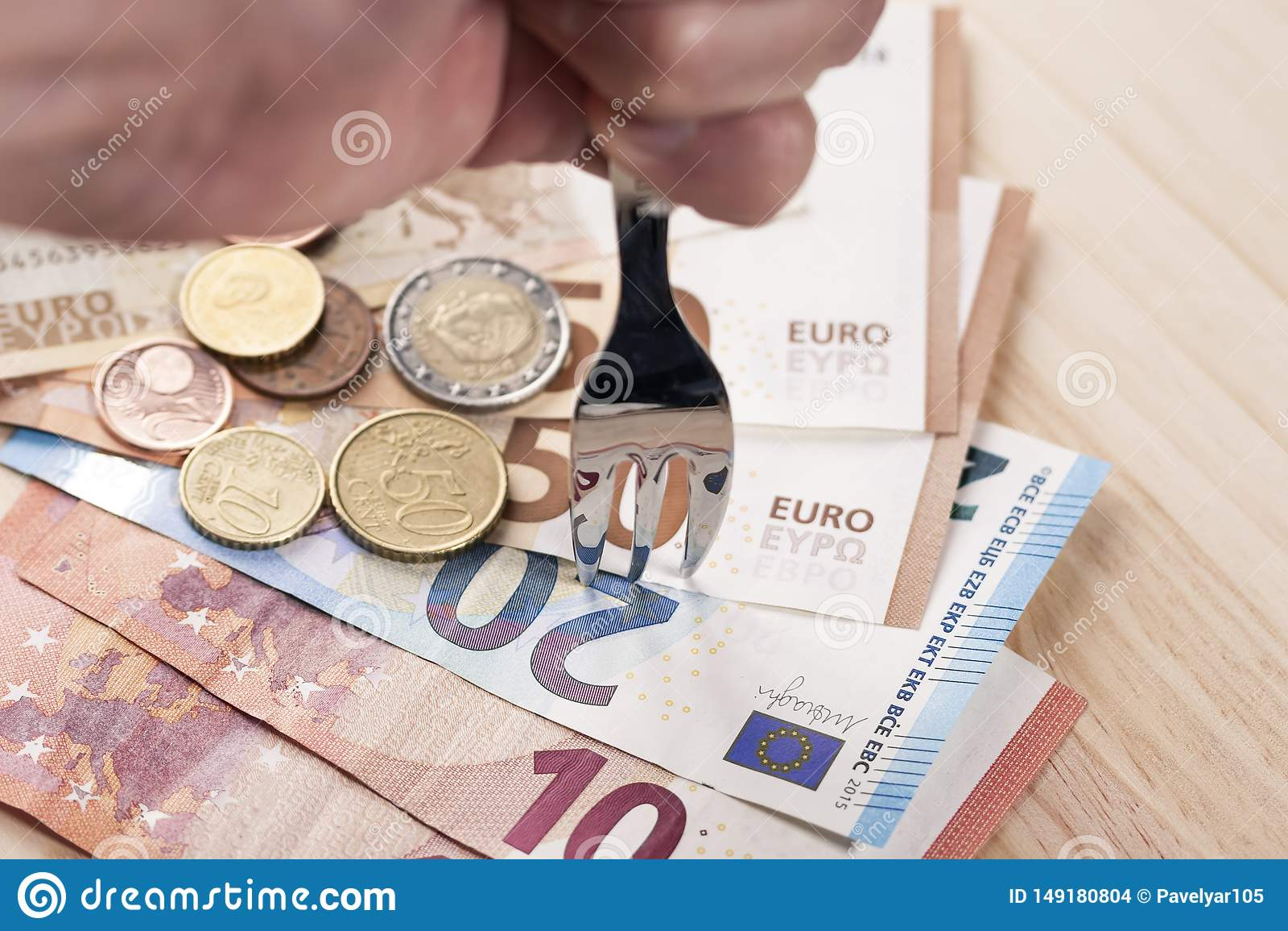 En hand med en skinande metallisk gaffel slår en hög av sedlar och euromynt