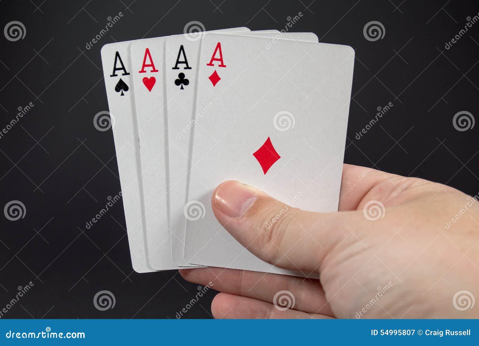 En hand som rymmer de fyra överdängarna från att spela kort
