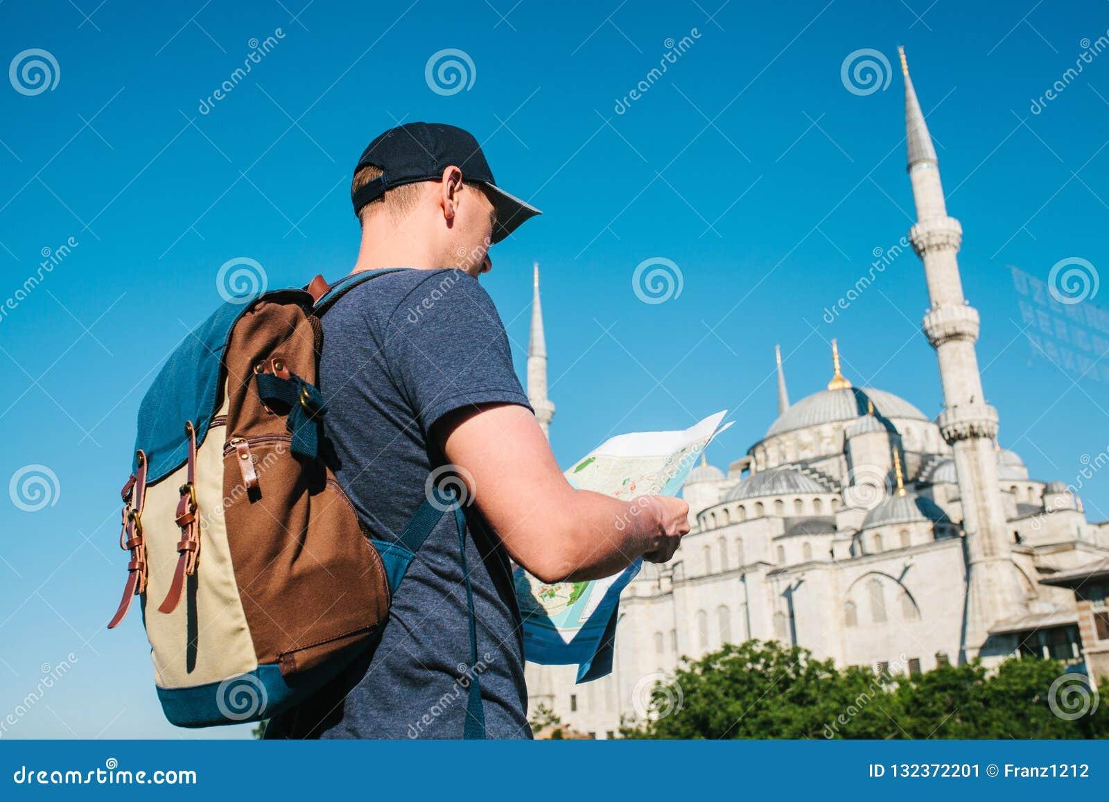 En handelsresande i en baseballmössa med en ryggsäck ser översikten bredvid den blåa moskén - den berömda sikten av