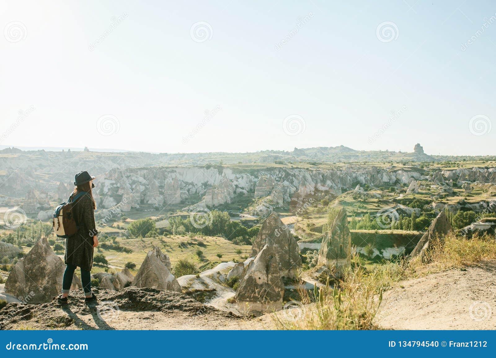 En handelsresande i en hatt med en ryggsäck står på ett berg och ser en härlig sikt i Cappadocia i Turkiet resa