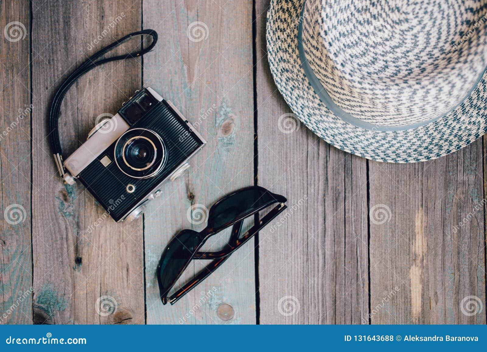 En hatt, en gammal kamera och solglasögon på trätabellen