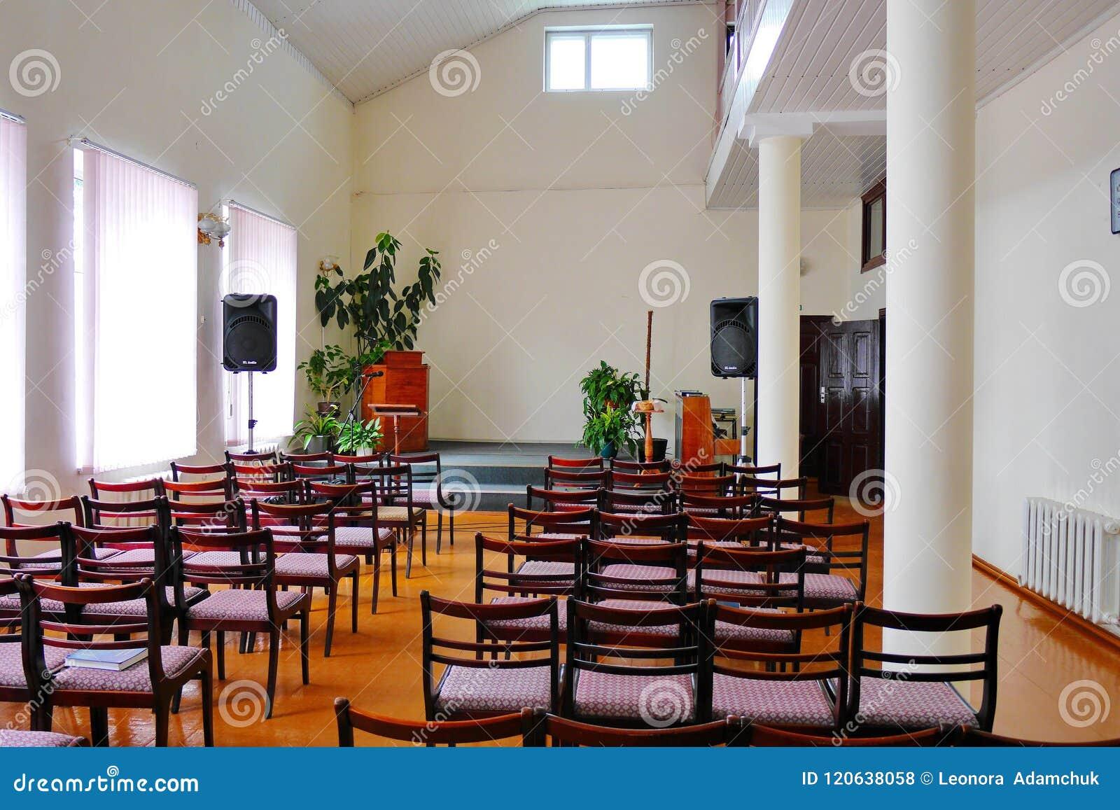 En hemtrevlig korridor i ett rum med höga tak och vita väggar med rader av stolar och en etapp med högtalare för en mikrofon och