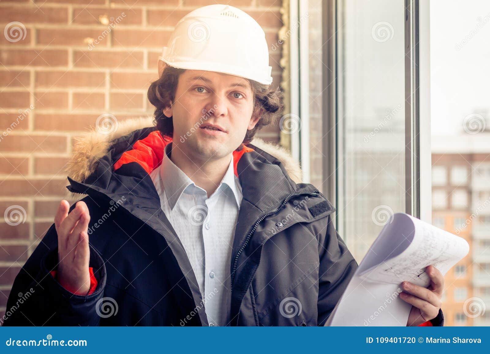 En ilsken missnöjd byggmästarearbetare i en hjälm med projektteckningsplan i hans en hand och mobiltelefon i andra