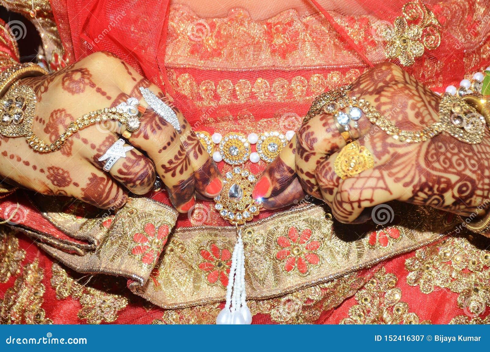En indisk brudgum som visar hennes guld- bukbälte som fästas ovanför sareen