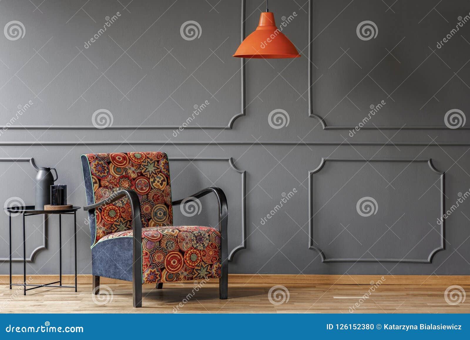 En industriell sidotabell och en bohofåtölj i en elegant grå vardagsruminre med stöpningen och ställe för en coffetabell Beträffa