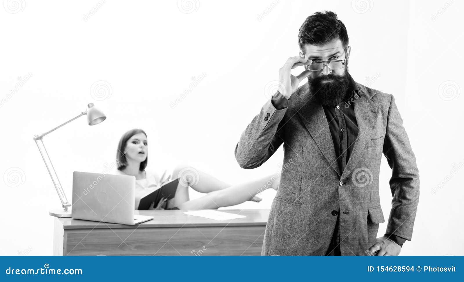 En intellektuell blick av hipsteren Hipster som fixar hans exponeringsglas medan sexig kvinna som arbetar i bakgrund Sk?ggig hips