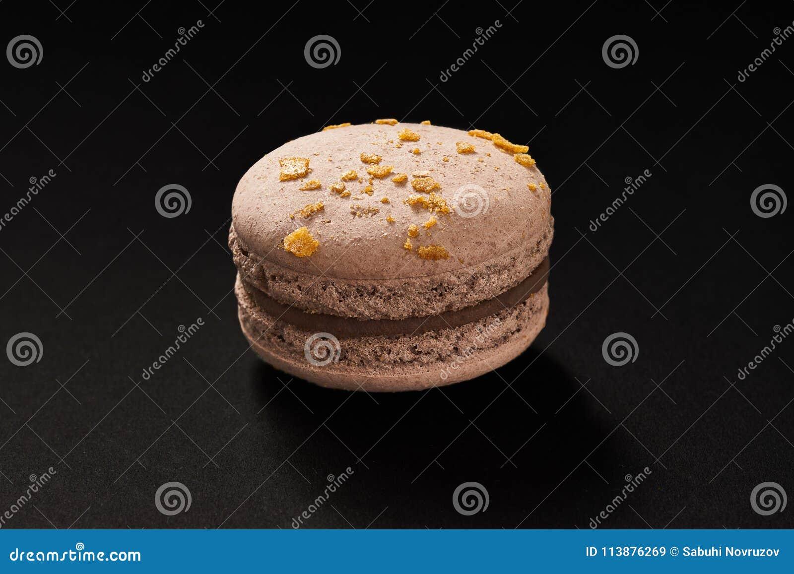 En kaka av makaronibruntfärg Läcker chokladmakron som isoleras på svart bakgrund Fransk söt kaka